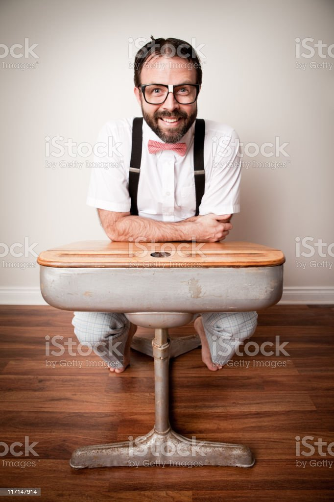 Color Image of Nerdy Man Student Sitting at School Desk stock photo