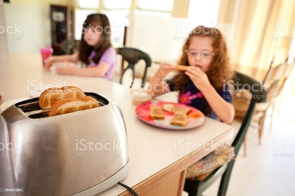 Color Image of Sisters Eating in Their Kitchen at Home stock photo