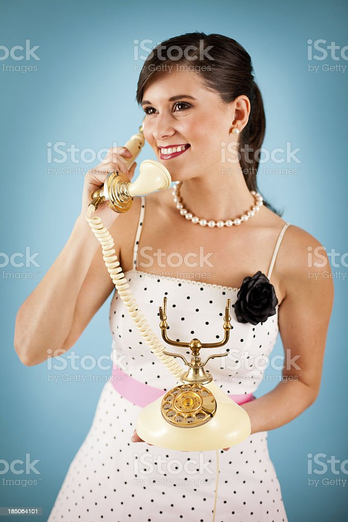 Color Image of Smiling Retro Gal Holding a Vintage Telephone royalty-free stock photo