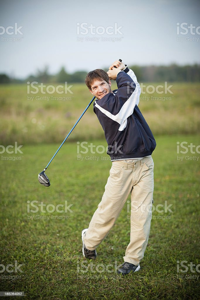 Color Image of Teenage Boy Swinging Golf Club Outdoors royalty-free stock photo