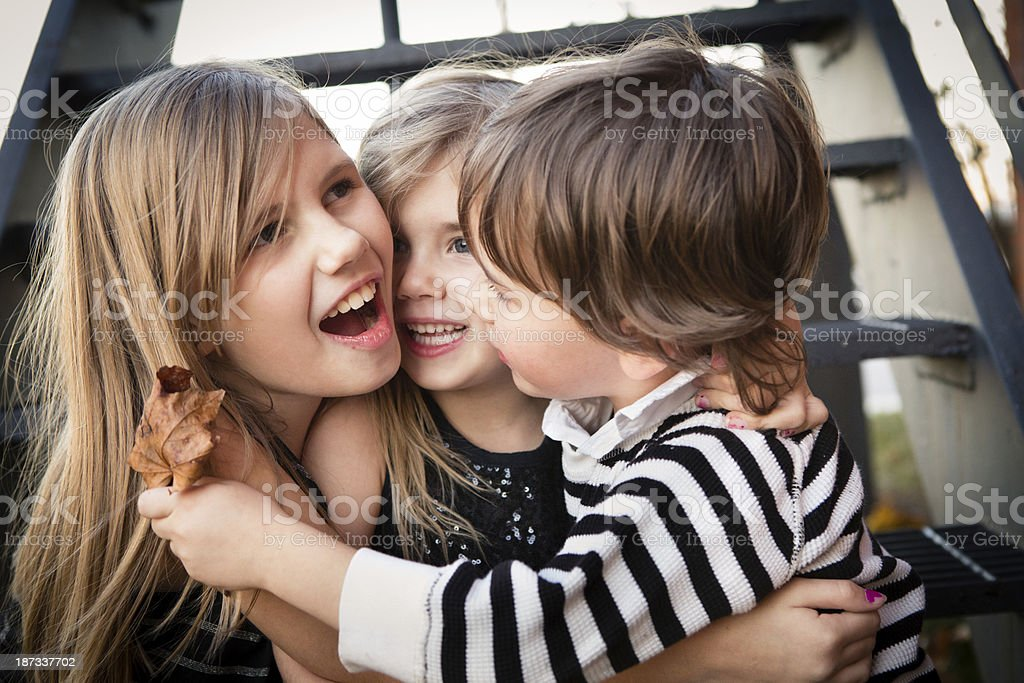Color Image of Two Sisters and Their Little Brother Hugging royalty-free stock photo