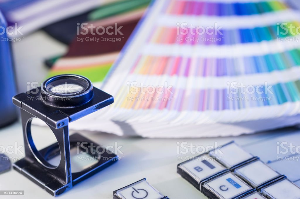 Color management process with magnifying glass and color swatches stock photo