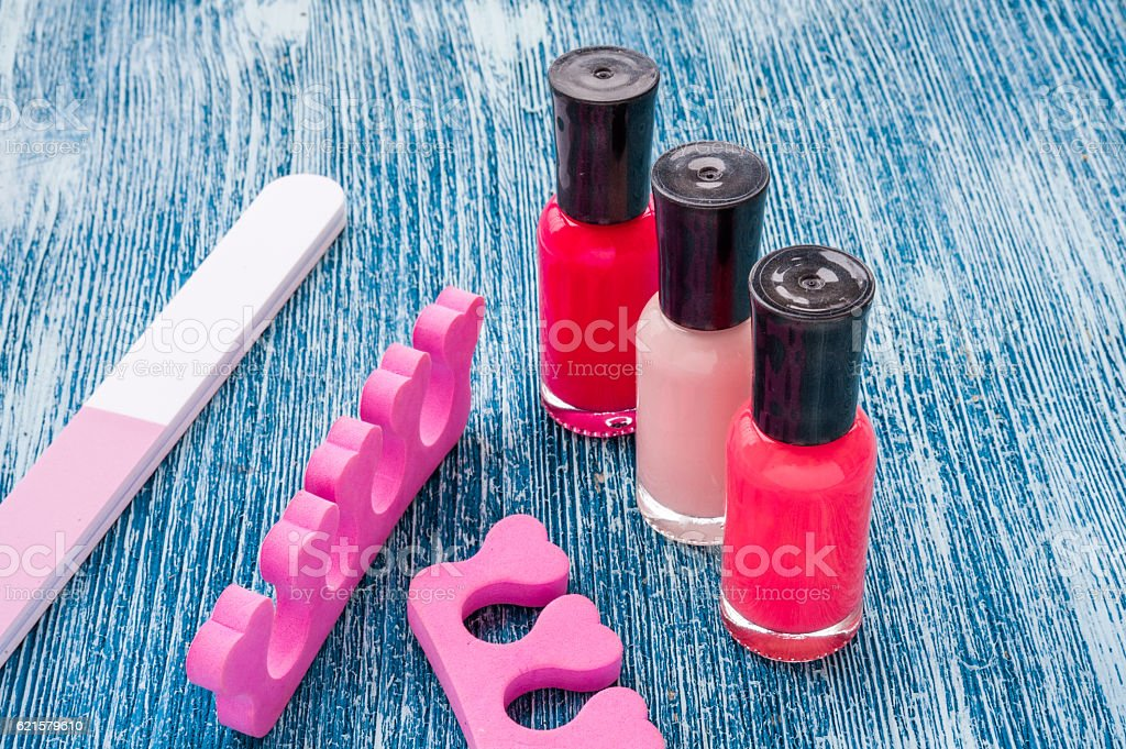 color nail polish with pedicure set on blue background stock photo