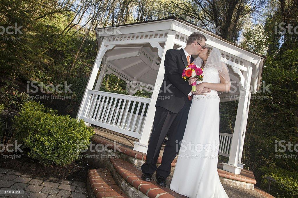 Color Newlyweds Kissing Groom Holding Bride Outside Gazebo Wooded Background royalty-free stock photo