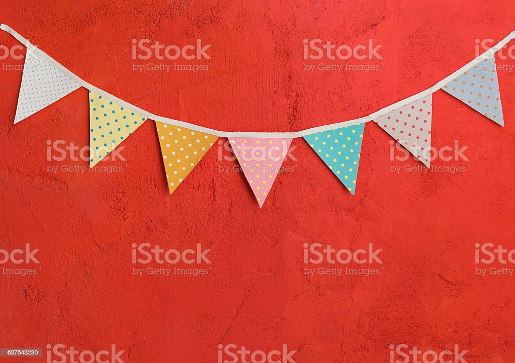 Color party flags on red cement wall stock photo