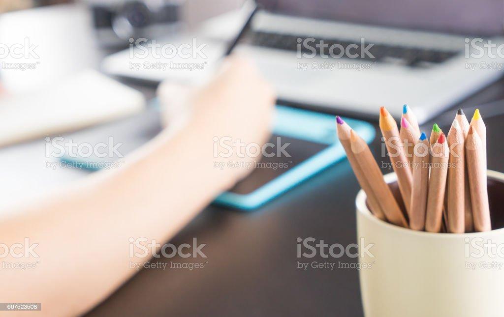Color pencils in a mug on graphic designer desktop stock photo