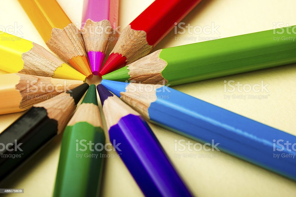 Color pencils in arrange in color wheel colors on paper background stock photo