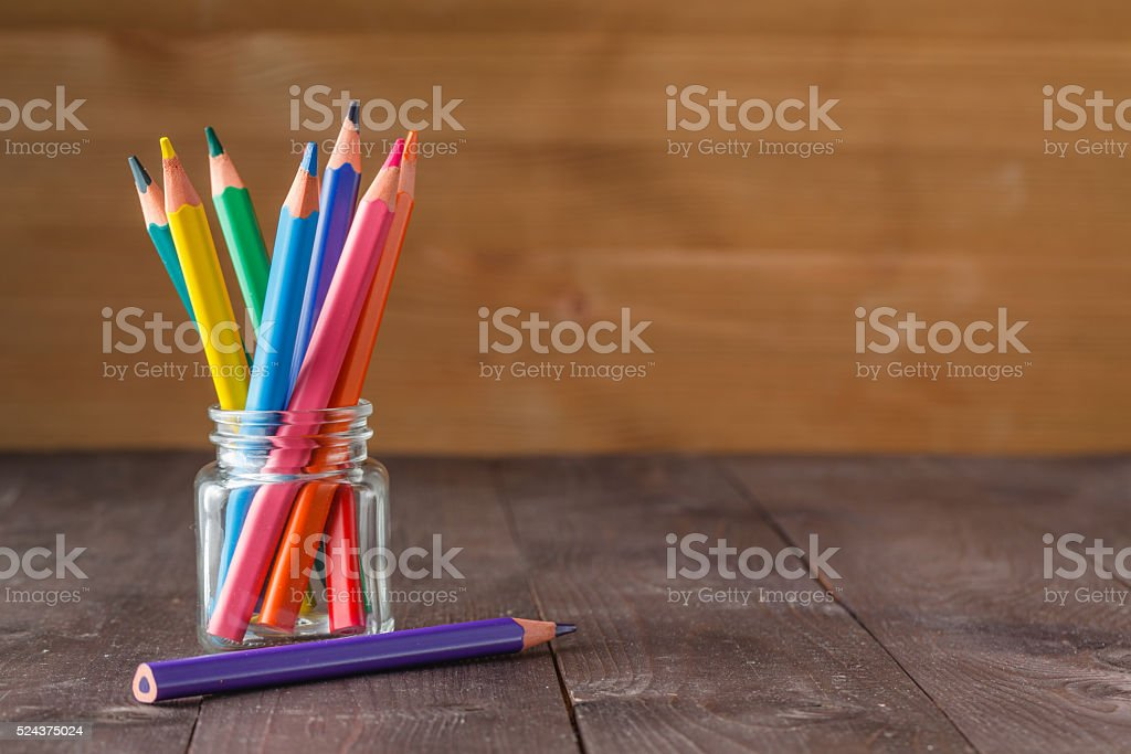 Color pencils in glass jar on wooden background stock photo