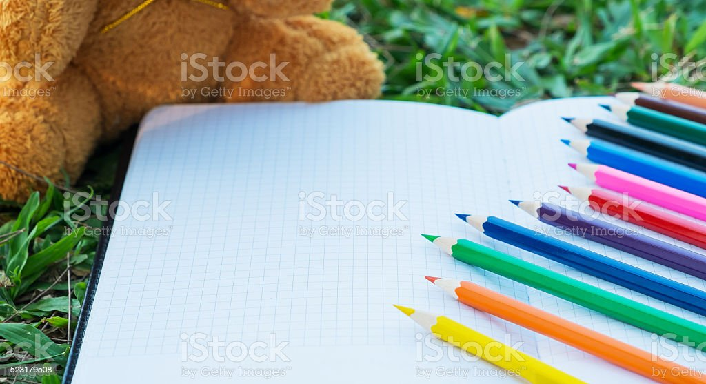Color pencils on grid notebook stock photo