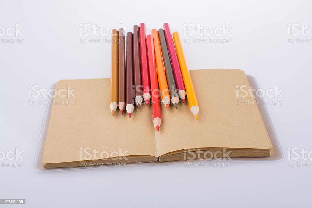 Color pencils placed on a notebook stock photo