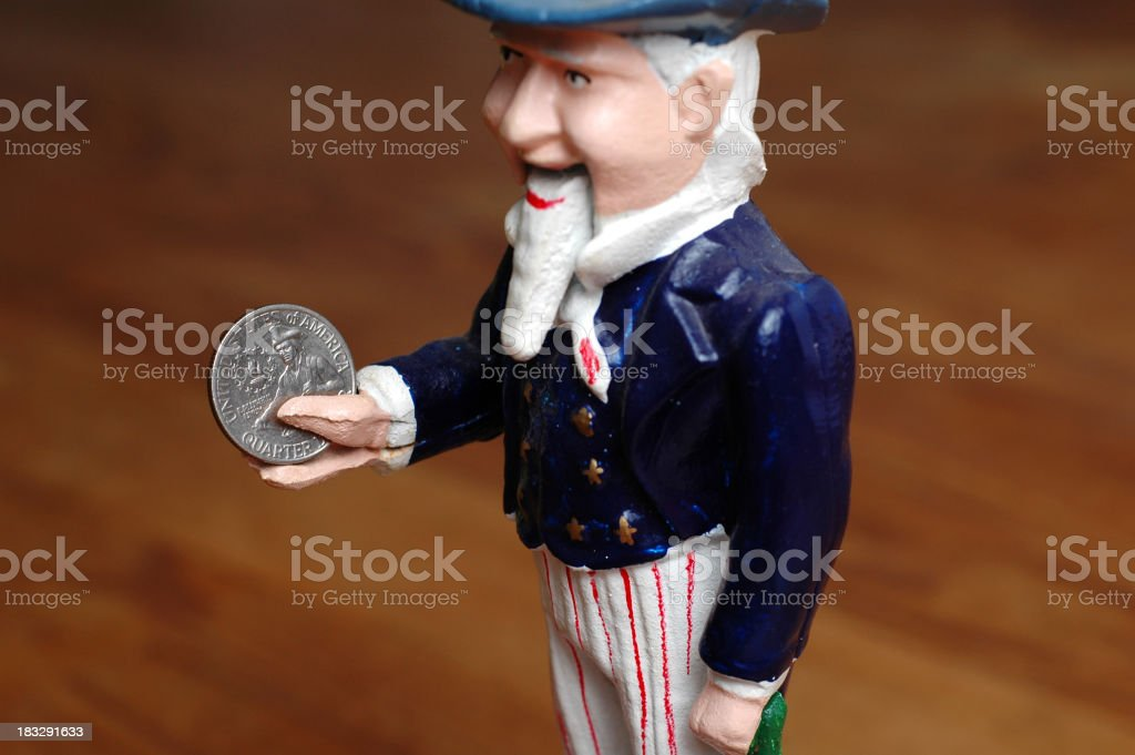 Color Photo of Vintage Metal Uncle Sam Bank Holding Quarter stock photo
