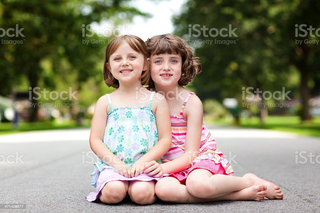 Color Portrait of Two Happy Sisters Hugging on Street royalty-free stock photo