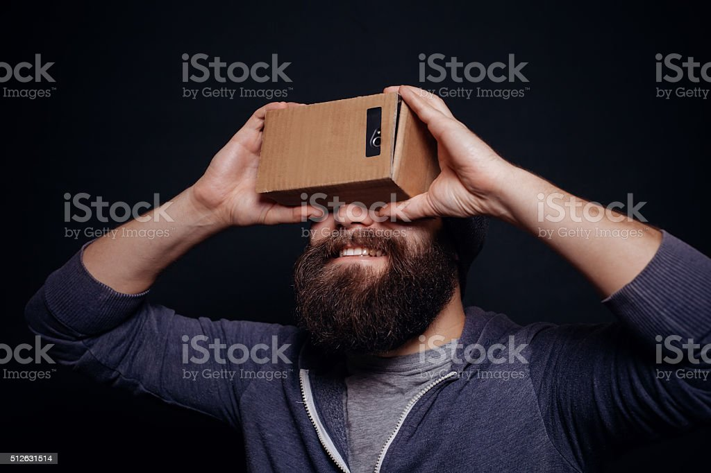 Color shot of a young man looking through card board stock photo