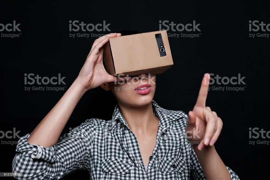Color shot of a young woman looking through cardboard stock photo
