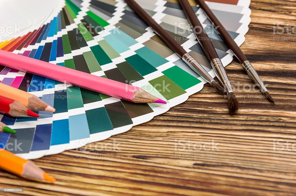 color swatches book with pencils and brush stock photo