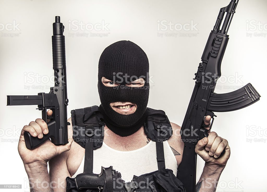 Color Terrorist Wielding Machine Guns Close Up Staring Gritty stock photo