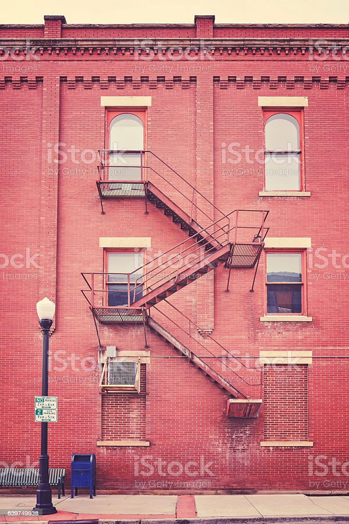Color toned building wall with fire escape stairs, USA stock photo