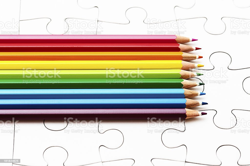 Color your own jigsaw! Colorful pencil crayons on blank puzzle stock photo