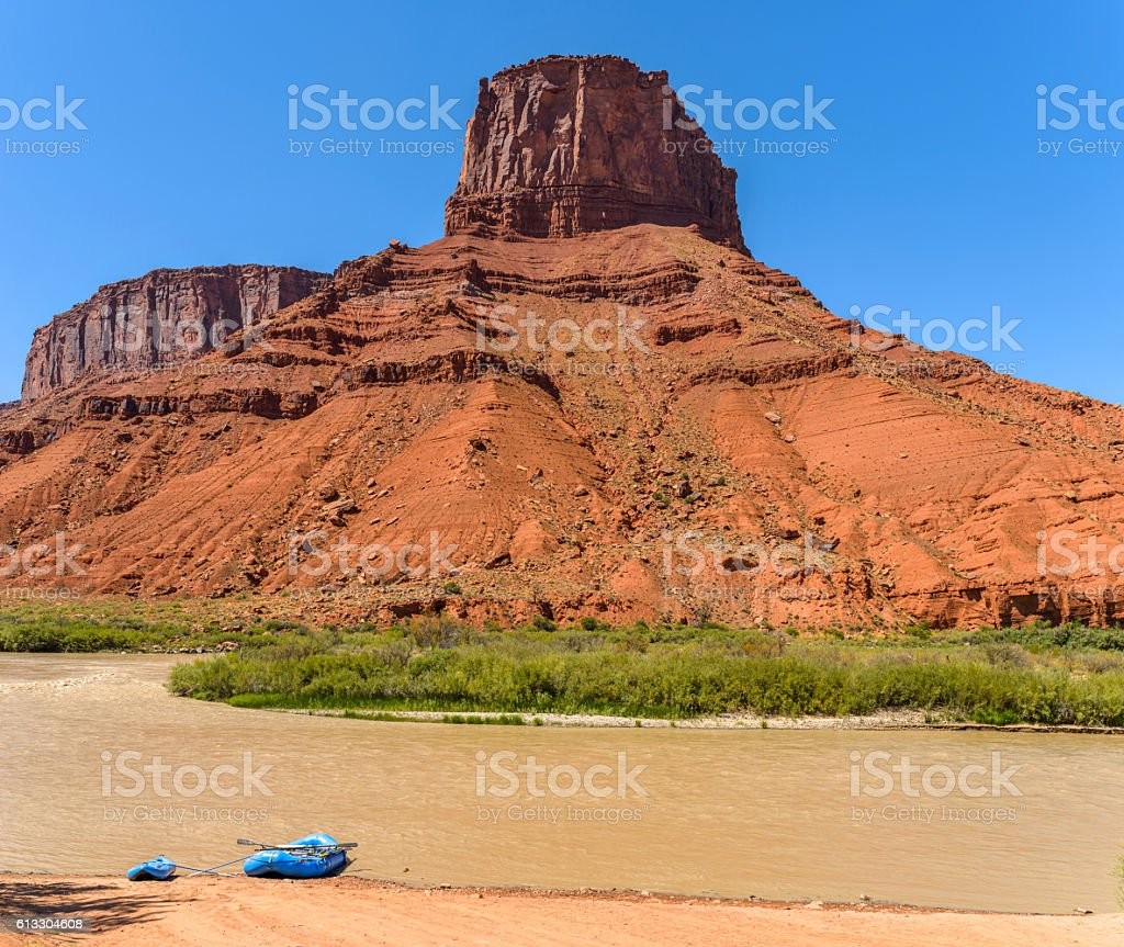 Colorado River running at base of a big red sandstone butte in Castle...