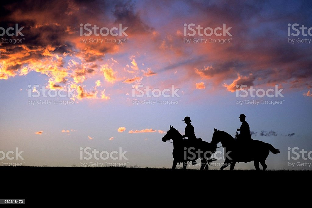 Colorado sunset silhouette horseback riders copy space stock photo