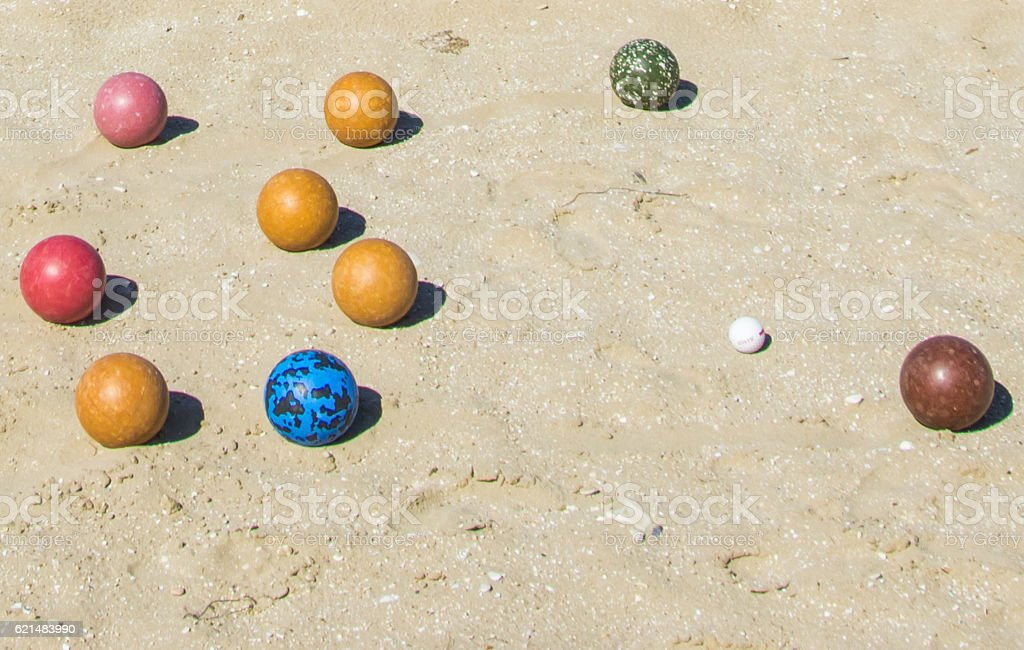 Colored balls for bowling on sand. stock photo