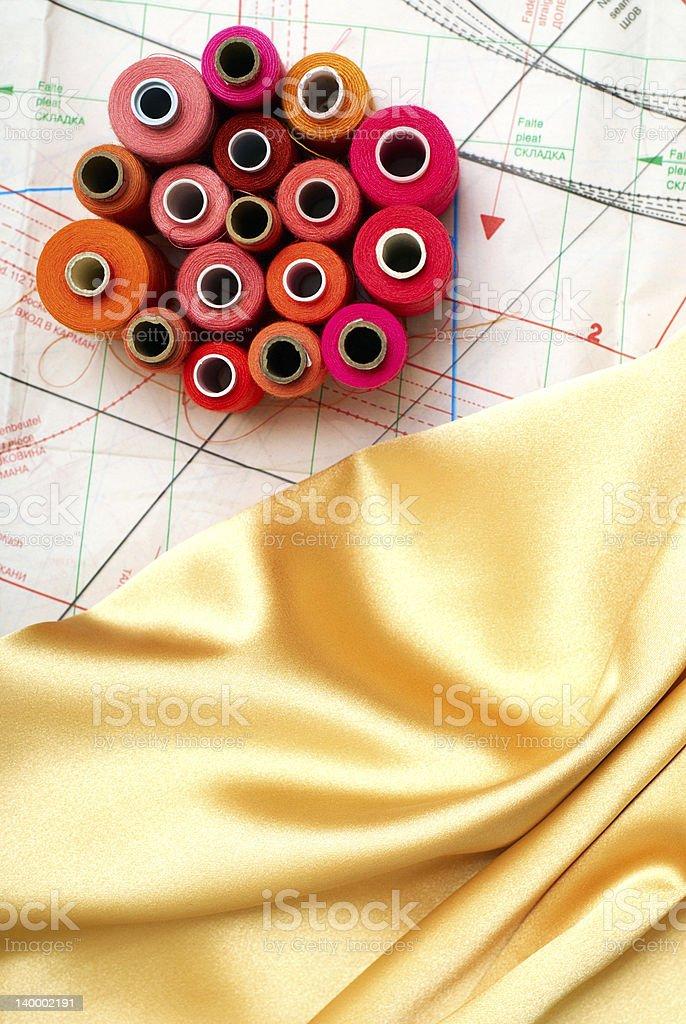 colored bobbins and golden silk stock photo