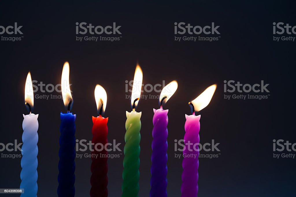 Colored candles on black background. six pieces. each candle silhouette stock photo