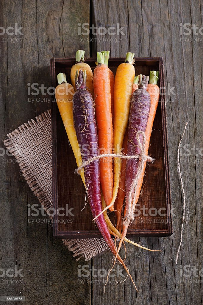 Colored carrots over rustic wooden background stock photo