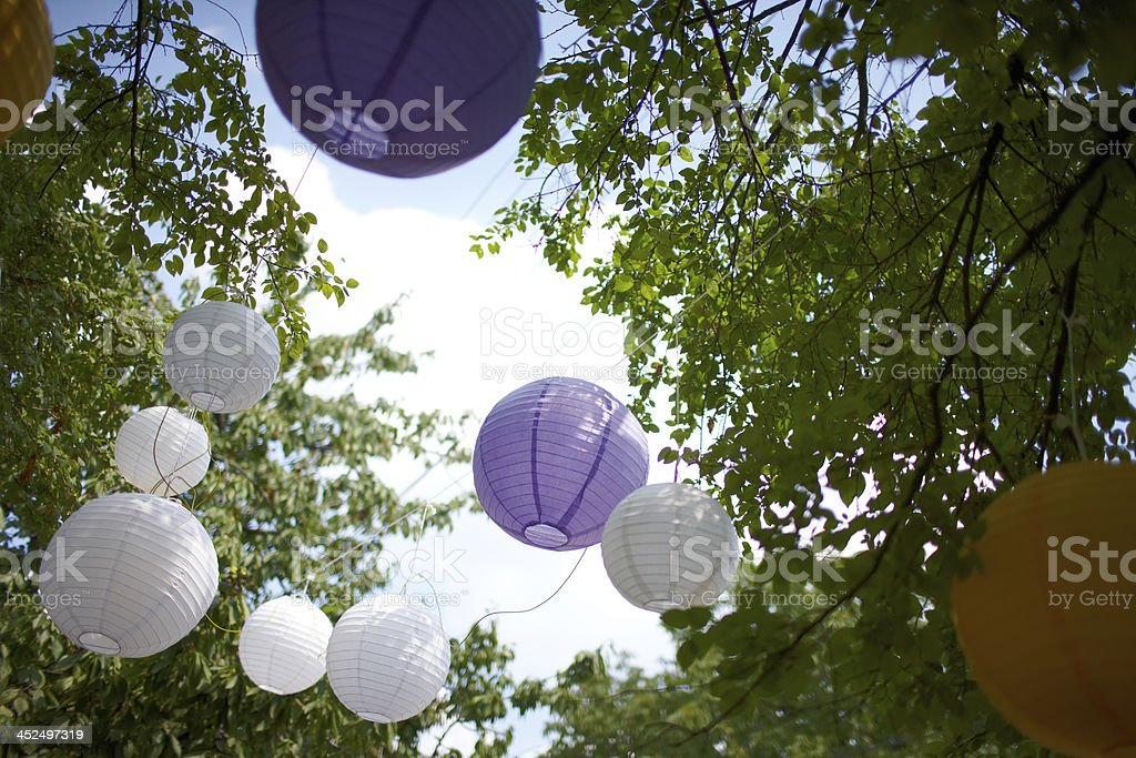 Colored  decorations hang from the trees at a wedding stock photo