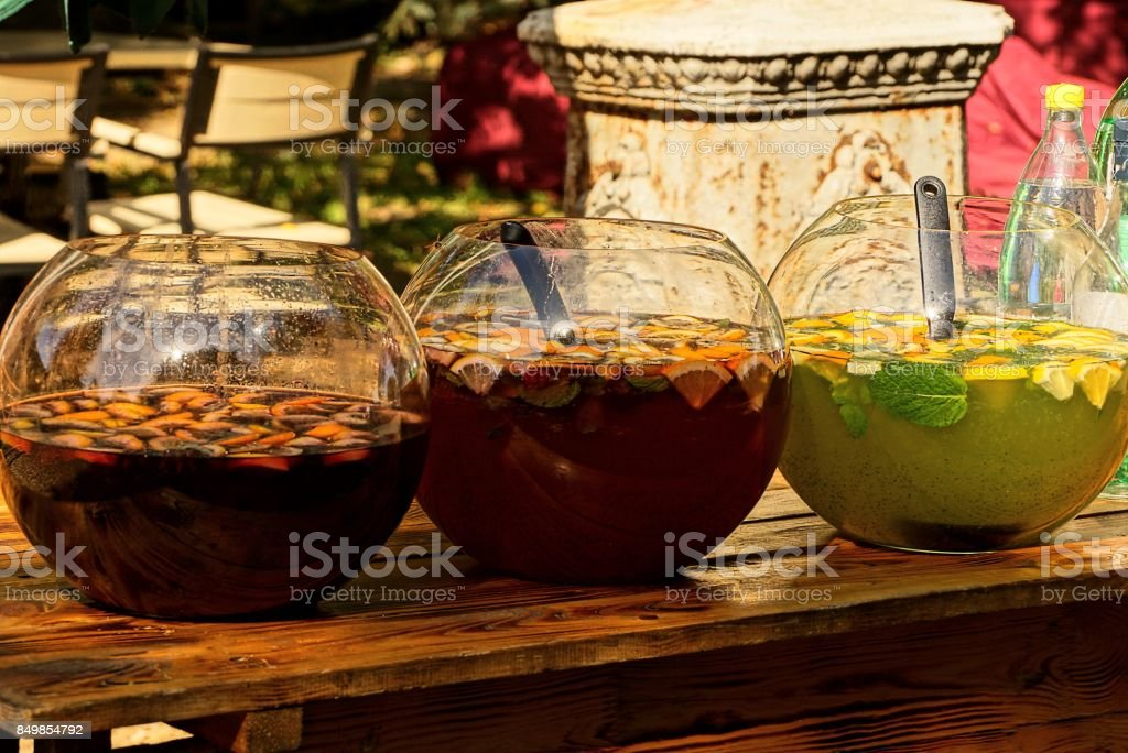 Colored drinks in large glass jars on a wooden table stock photo