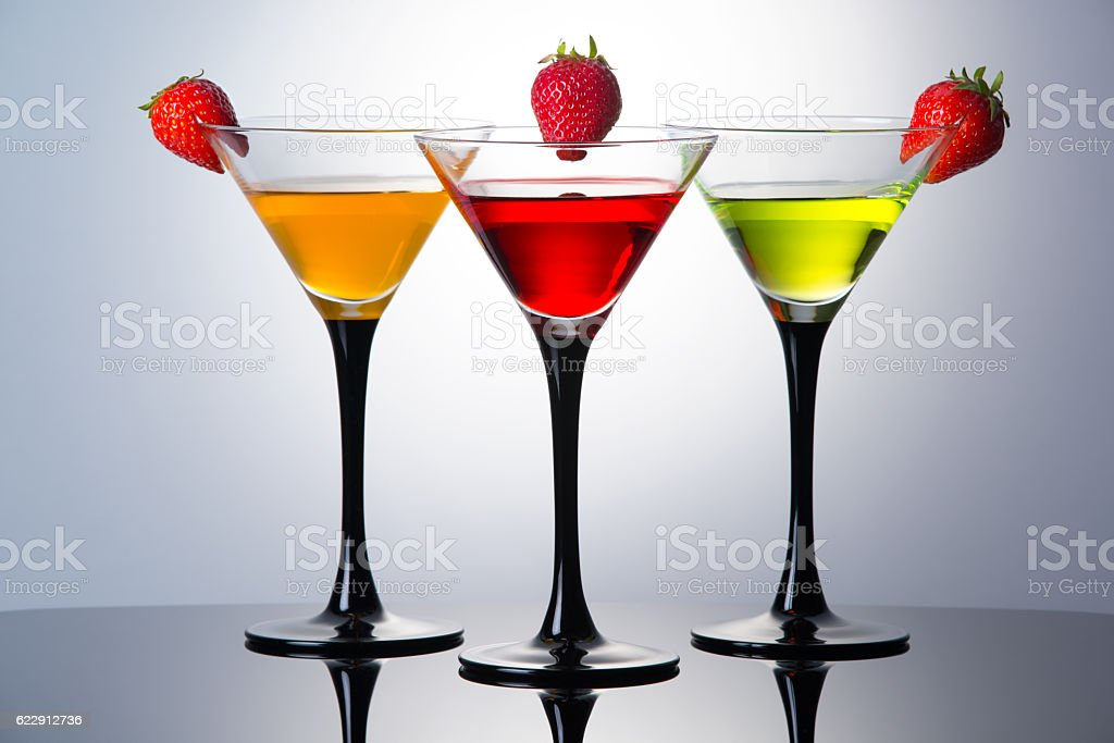 Colored drinks in martini glasses with strawberries, cocktails with liqueurs stock photo