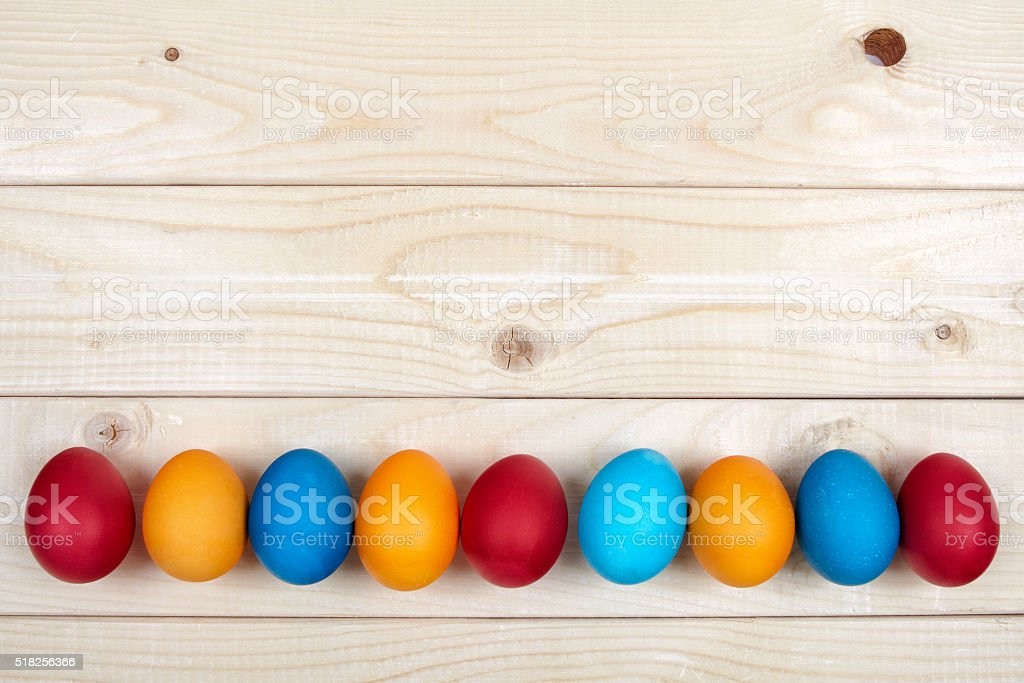 Colored Easter eggs decoration line over the light wooden surface stock photo