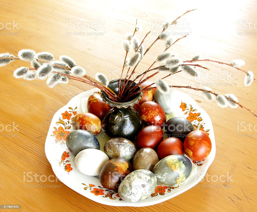 colored easter eggs on plate with pussy willow stock photo
