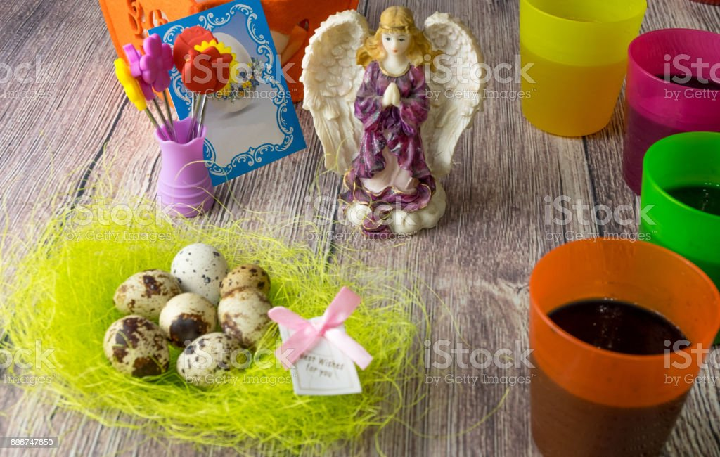 Colored Easter eggs table decoration with angel stock photo