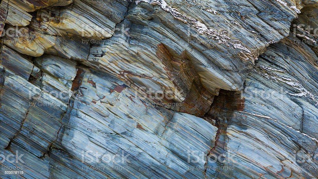 Colored granite and schist rock face stock photo