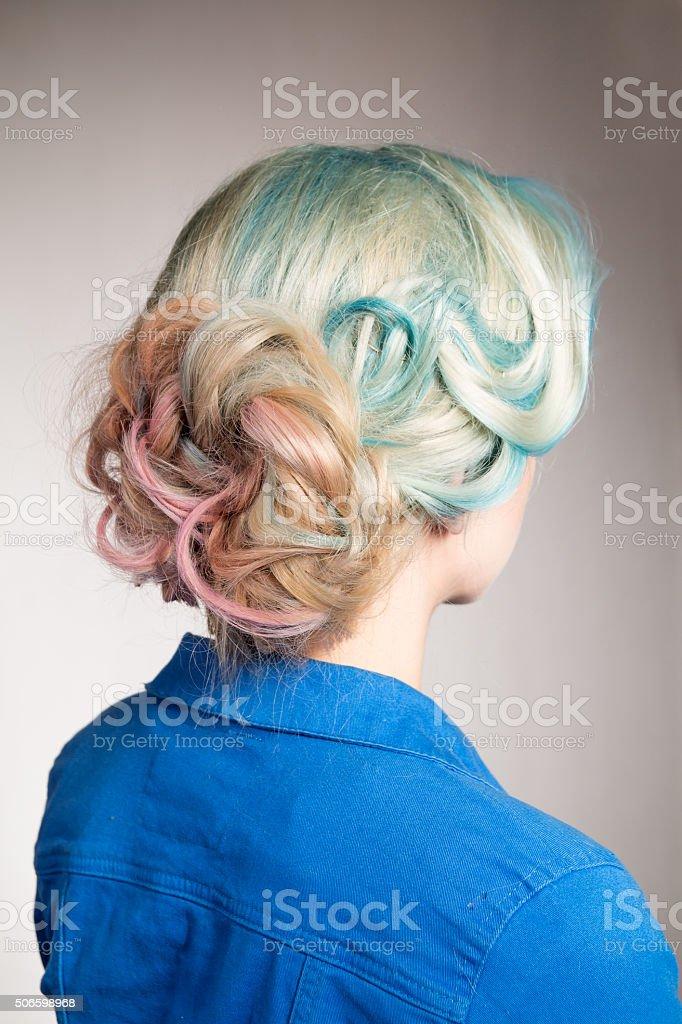 Colored hair and a bun on girl's head stock photo