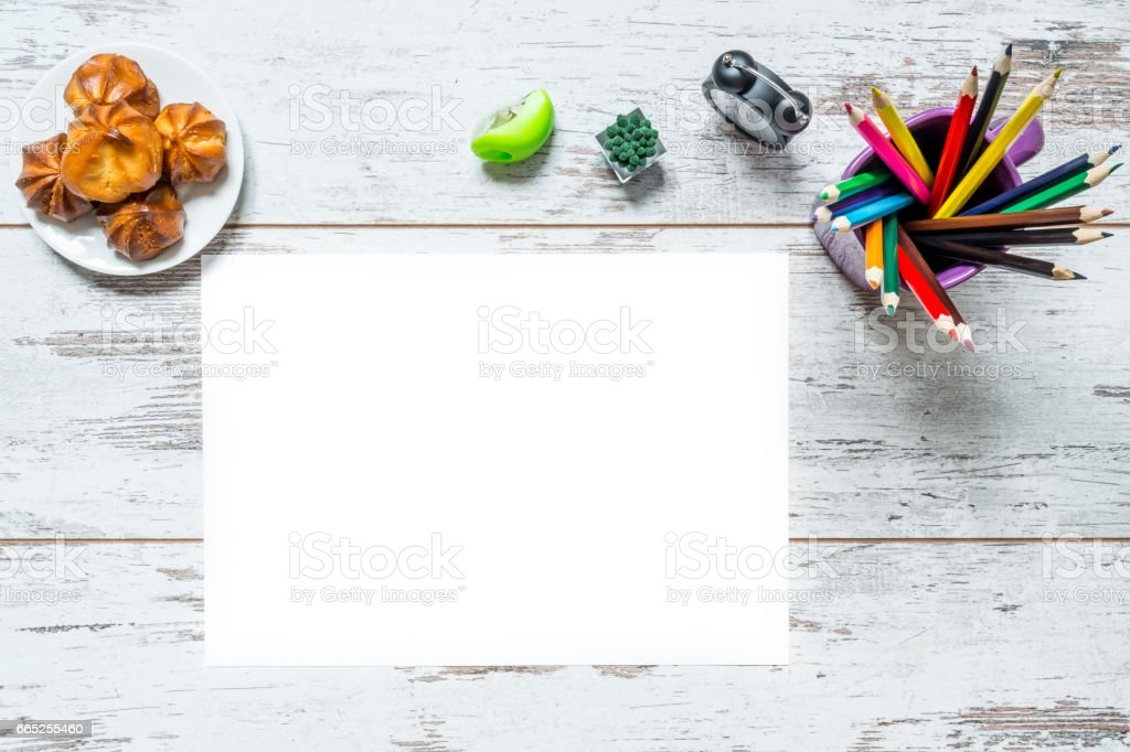 Colored multicolored pencils, a sheet of white paper isolated, old style clock, plate with cake on a vintage wooden background, wooden worn boards with cracks. stock photo