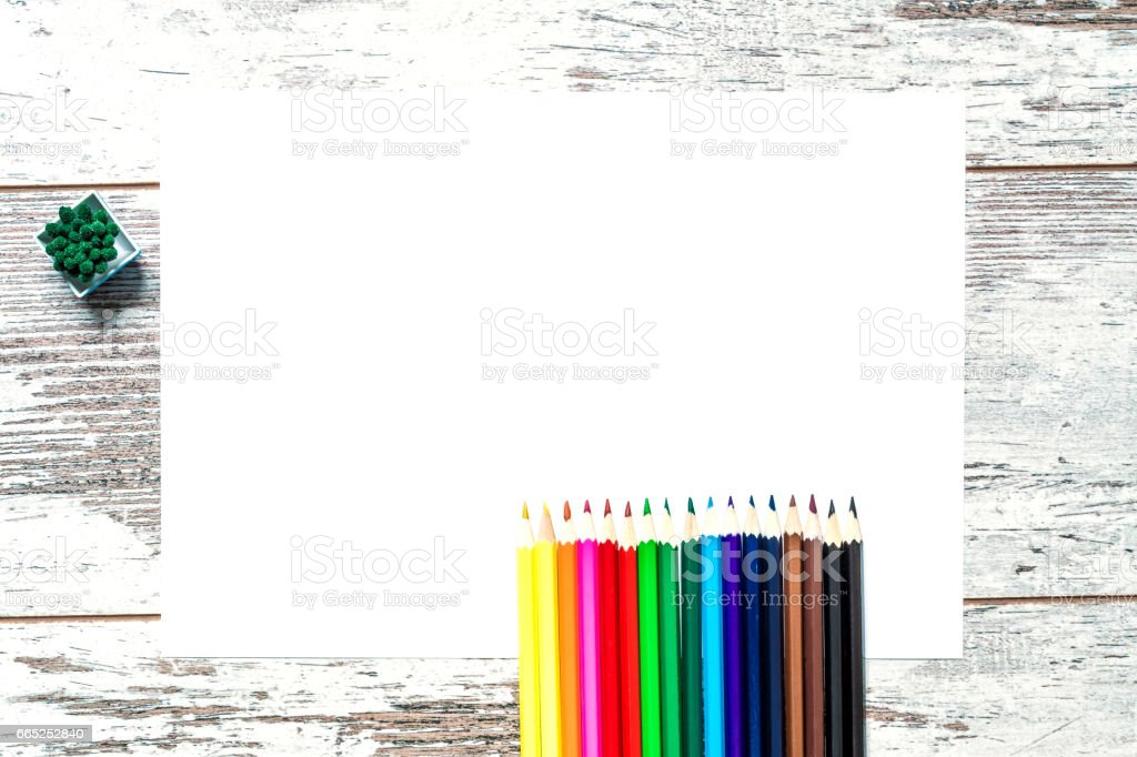Colored multicolored pencils, a sheet of white paper isolated on a vintage wooden background, wooden worn boards with cracks. Top view. stock photo