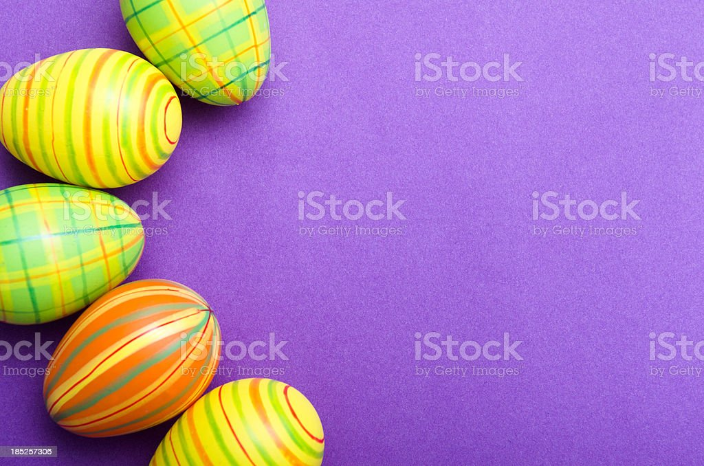 Colored Painted easter egg on purple background stock photo