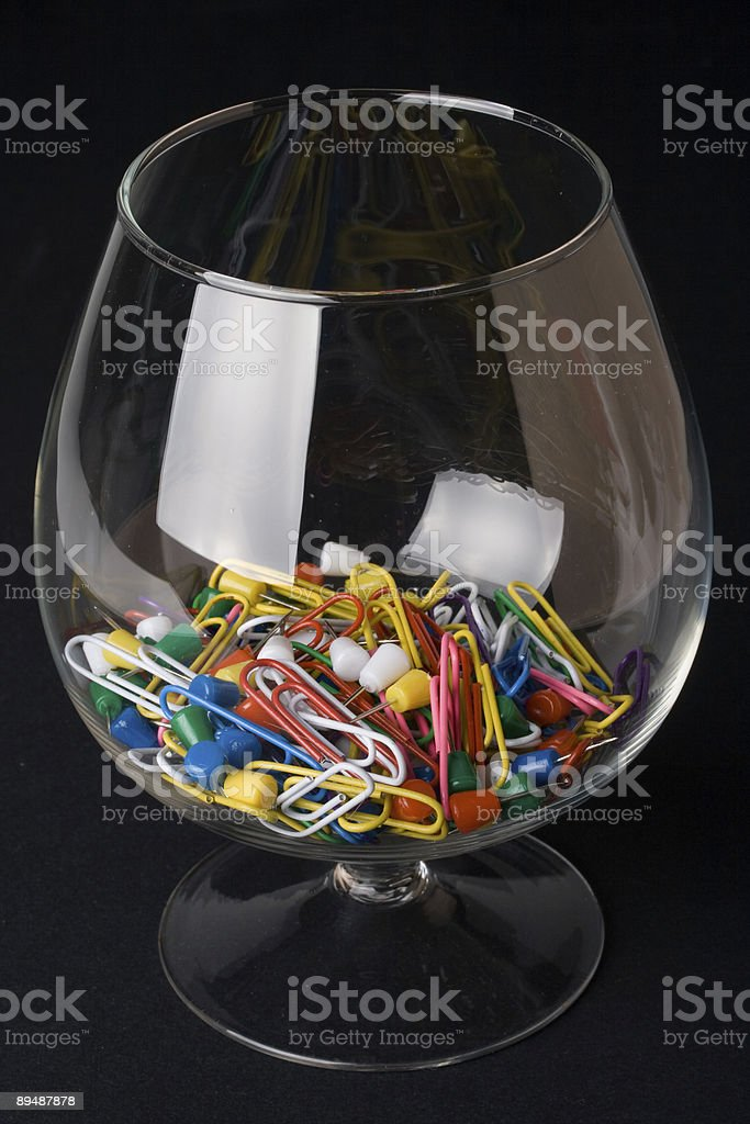 Colored paperclips and pins in a glass royalty-free stock photo