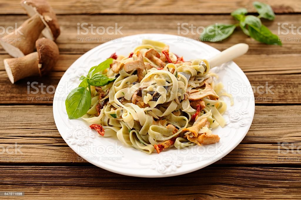Colored pasta with wild mushrooms and basil stock photo