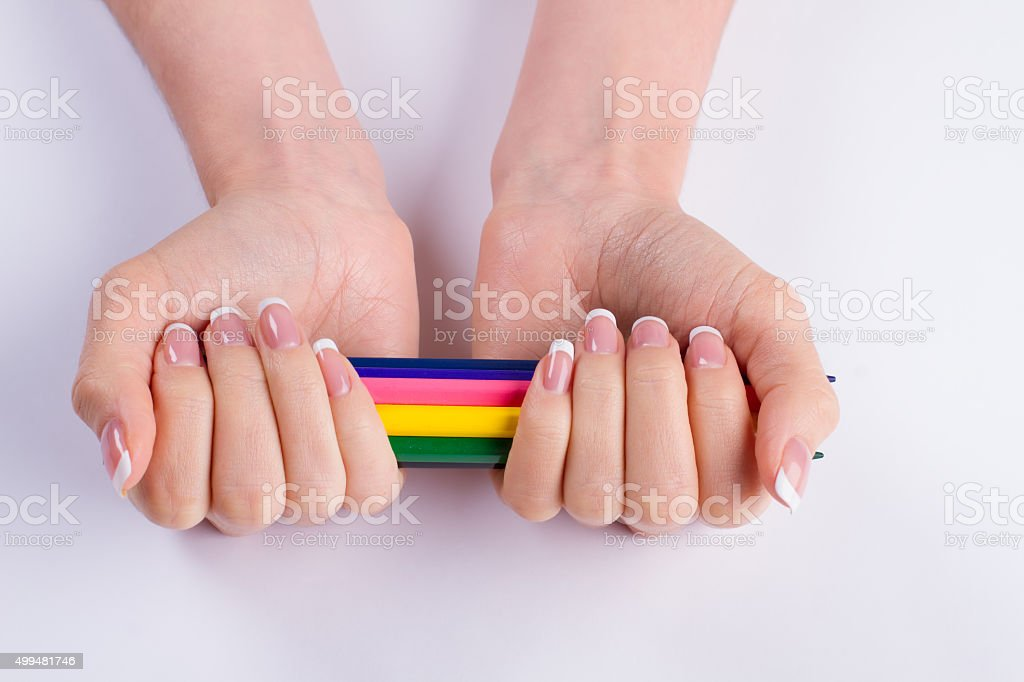 Colored pencils in a beautiful female hands. stock photo