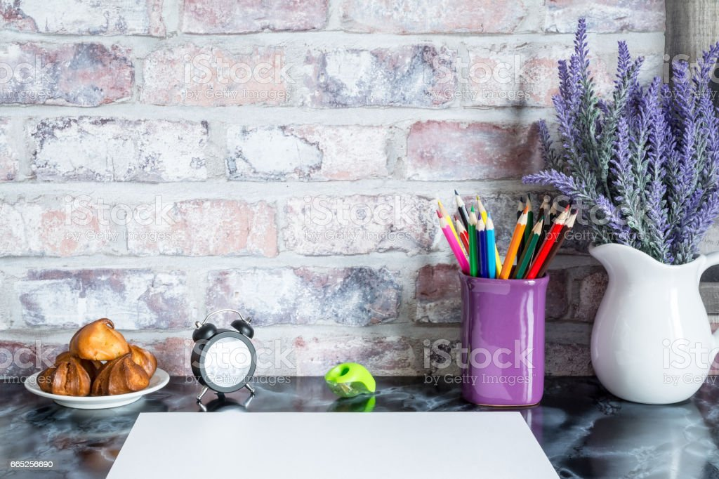 Colored pencils in a mug, vase of lavender flowers, clock, plate of cakes, white paper on a table against a brick vintage wall. stock photo