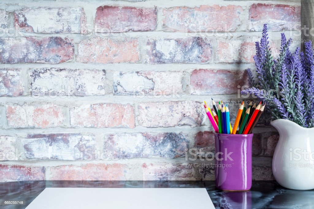 Colored pencils in a mug, vase of lavender flowers, white paper on a table against a brick vintage wall. stock photo
