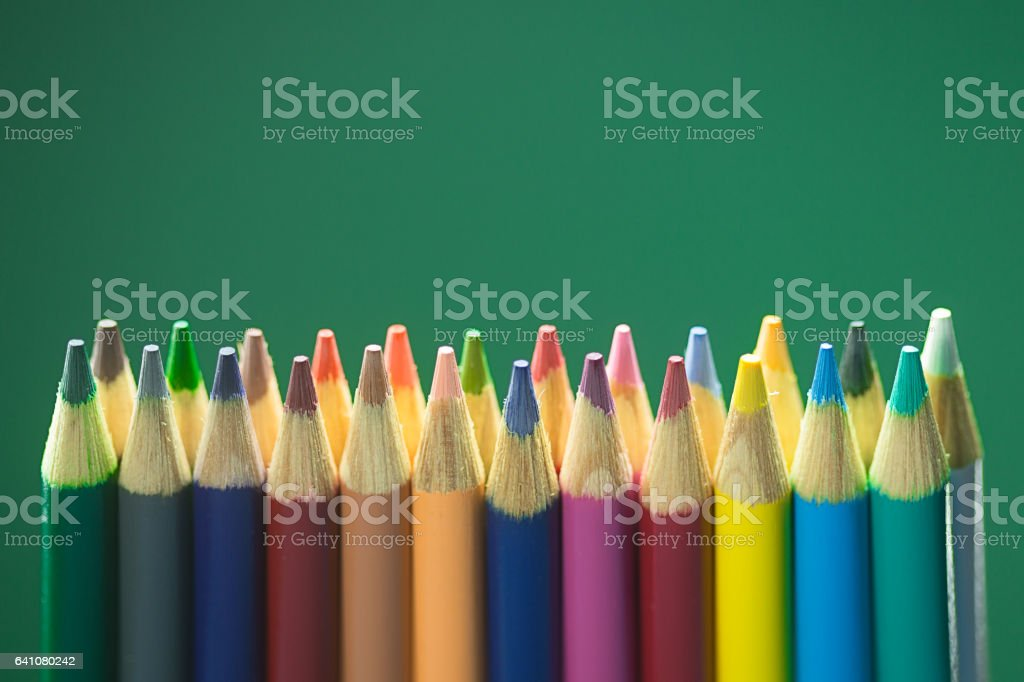 Colored Pencils on Green Backdrop.jpg stock photo