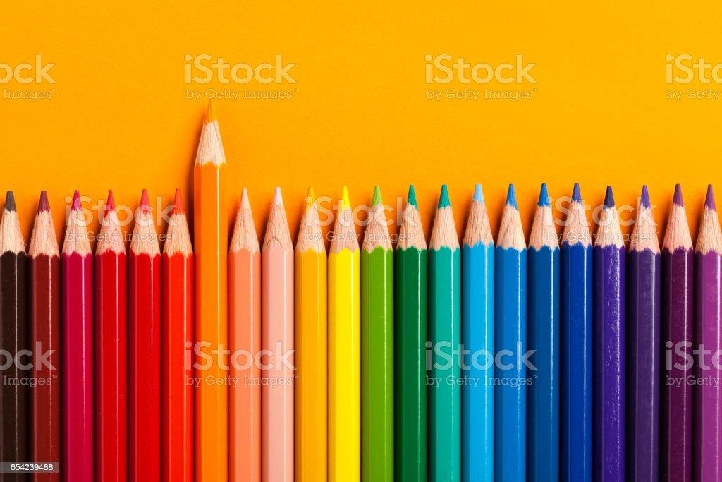 Colored Pencils on orange paper stock photo