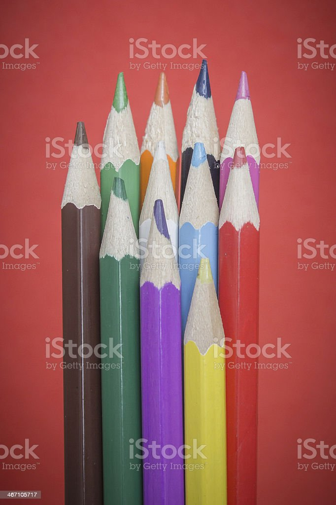 Colored pencils on red background stock photo