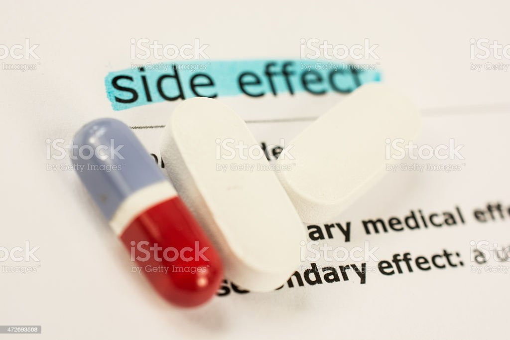 Colored pill and capsules on sheet of medicinal side effects stock photo