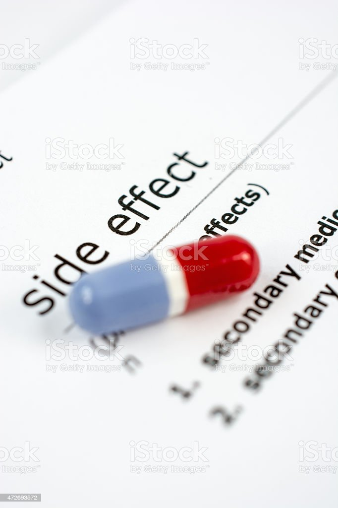 Colored pill on sheet of adverse medicinal side effects stock photo