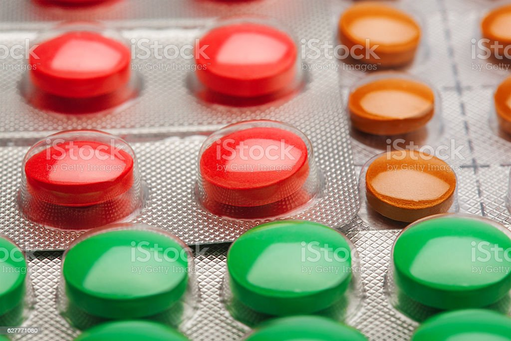 Colored pills in a plastic silver boxes stock photo